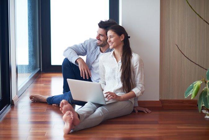 Man en vrouw zitten met laptop op vloer