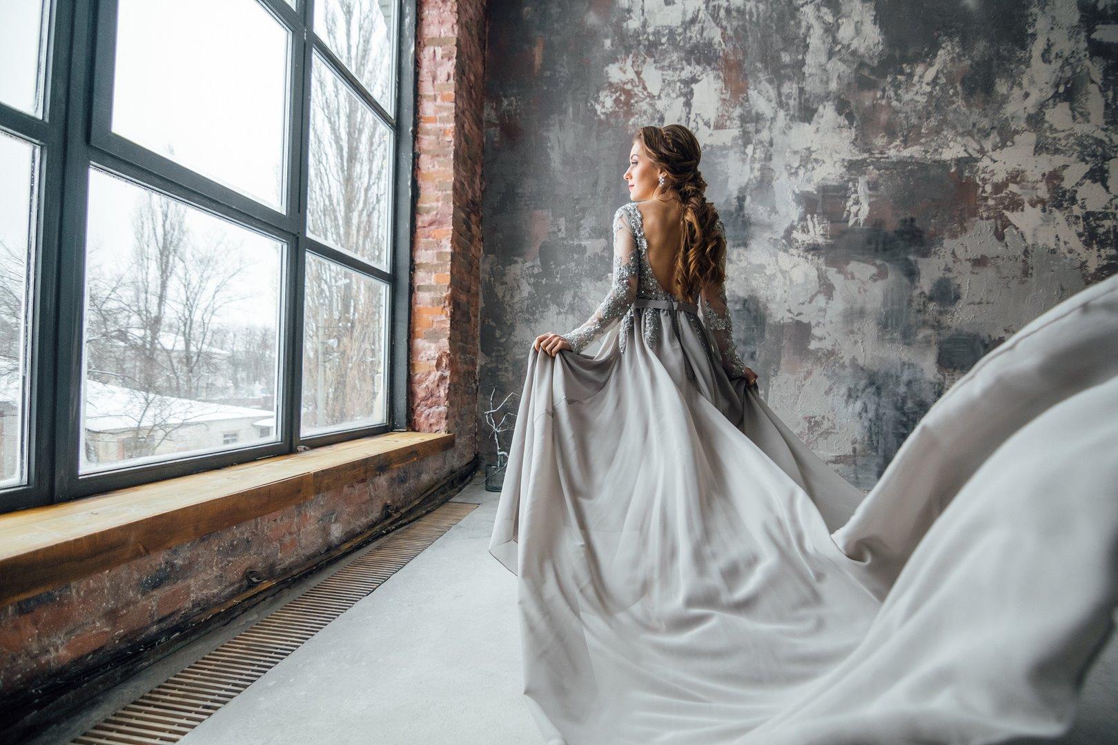 Vrouw in grijze jurk kijkt door raam naar buiten